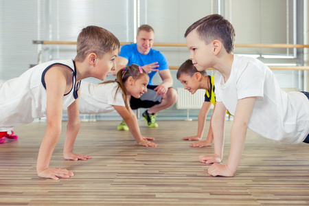 Happy sporty children in gym. pressing, working with a coach. childrens fitness Фото со стока