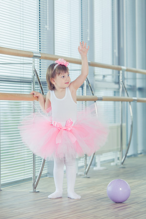 art lessons: Little ballerina girl in a pink tutu. Adorable child dancing classical ballet in studio. Children dance. Kids performing. Young gifted dancer in a class. Preschool kid taking art lessons.