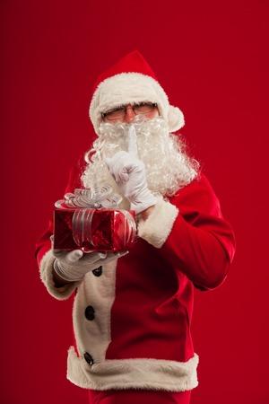 christmas Photo of kind Santa Claus giving xmas present and looking at camera. secret hand and lips Stock Photo
