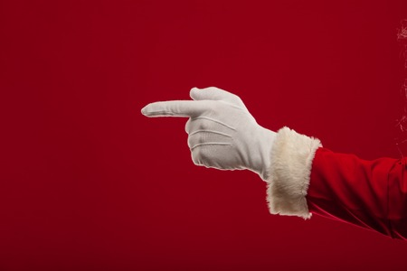Photo of Santa Claus gloved hand in pointing gesture. fingers. christmas