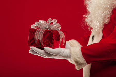 christmas Photo of Santa Claus gloved hand with red giftbox, on a red background Stock Photo