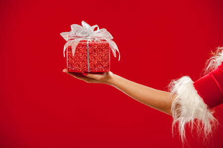 Christmas. Photo hand with red gift box, over red background.