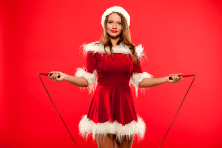 christmas, x-mas, winter, happiness concept - Sport, activity. Cute woman with skipping rope in santa helper hat , over red background Фото со стока