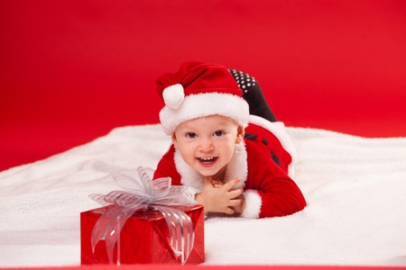 nappy new year: Beautiful little baby celebrates Christmas. New Years holidays. Baby in a Christmas costume with gift. Stock Photo