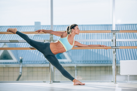 Woman stretching her leg at the barre. Imagens