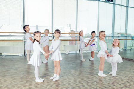 in unison: Group of little ballet dancers dressed in white