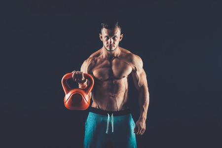 heavy weight: Fitness man doing a weight training by lifting a heavy kettlebell. Stock Photo