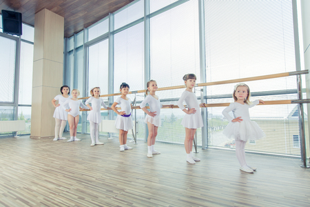 Group of seven little ballerinas standing in row and practicing ballet and using stick on the wall. They are good friend and amazing dance performers