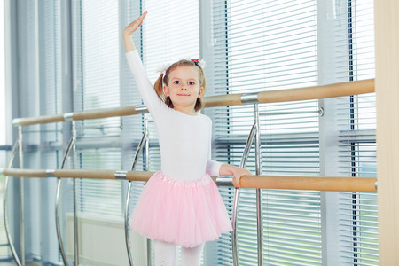 The young girl dances in a ballet tutu in the hall. Фото со стока