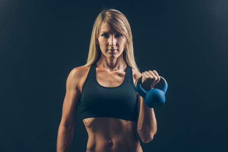 sweaty: Fitness woman exercising crossfit holding kettlebell strength training biceps. Beautiful sweaty fitness instructor on blackoard background looking intense at camera. Asian Caucasian female model Stock Photo