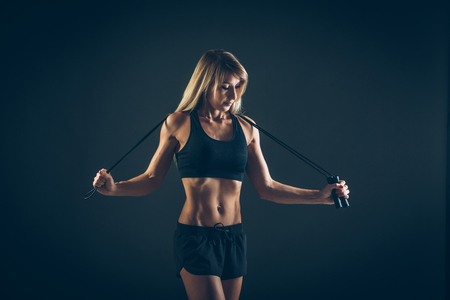 Sport, activity. Cute woman with skipping rope. Muscular woman  black background.