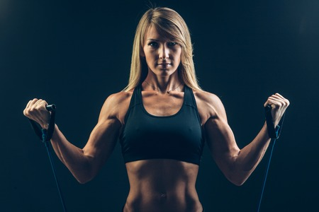 expander: Athletic young woman working on biceps with expander. Stock Photo