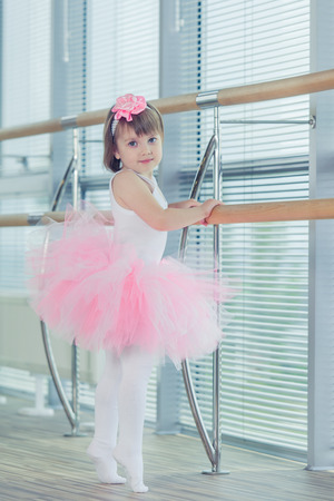 Little ballerina girl in a pink tutu. Adorable child dancing classical ballet in studio. Children dance. Kids performing. Young gifted dancer in a class. Preschool kid taking art lessons.