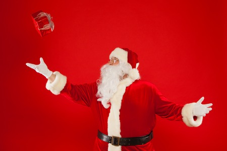christmastime: Photo of Santa Claus gloved hand with red giftbox, on a red background. Christmas