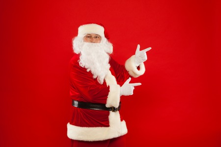 xmass: Santa Claus pointing in blank a place, red background.