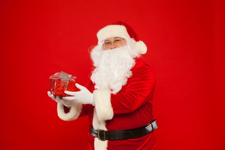 Photo of Santa Claus gloved hand with red giftbox, on a red background. Christmas