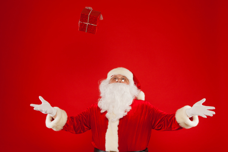 xmass: Photo of Santa Claus gloved hand with red giftbox, on a red background. Christmas