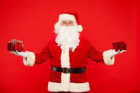 and guessing: Photo of Santa Claus gloved hands holding red giftbox. Stock Photo