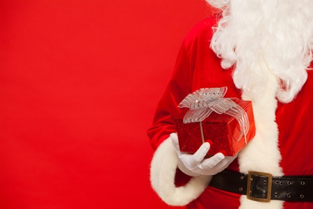 christmastime: Photo of Santa Claus gloved hands holding red giftbox. Stock Photo
