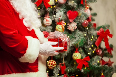 xmass: Santa Claus with giftbox on background of sparkling firtree. Stock Photo
