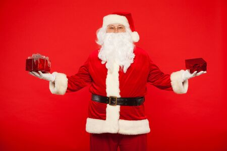 distributing: Photo of Santa Claus gloved hands holding red giftbox. Stock Photo