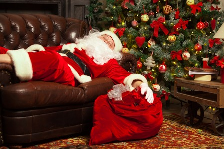 Santa Clause snoozing in a decorated living room with his sack full of gifts by his side.