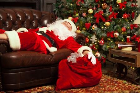 Santa Clause snoozing in een ingerichte woonkamer met zijn zak vol geschenken aan zijn zijde.