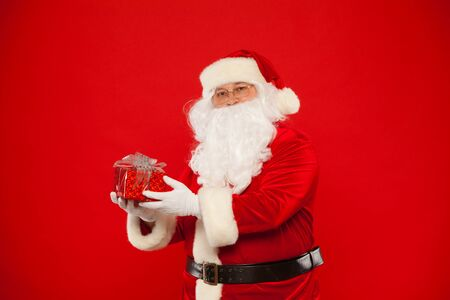 distributing: Photo of Santa Claus gloved hand with red giftbox, on a red background. Christmas