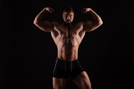 Rear view of healthy muscular young man with his arms stretched out isolated on black background. Stock Photo