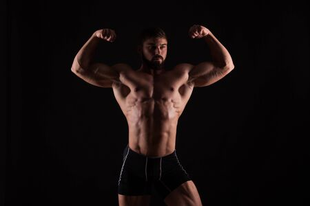 man power: Rear view of healthy muscular young man with his arms stretched out isolated on black background. Stock Photo