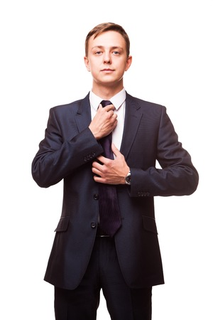 Stylish young man in suit and tie. Business style. Handsome man is standing, looking at the camera and fixing his tie Stock Photo