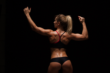 Beautiful athletic woman in sporty cloths is posing, holding hands up and showing her perfect body, back view isolated on dark background with copyspace