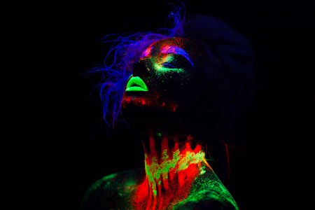 Beautiful extraterrestrial model woman with blue hair and green lips in neon light. It is portrait of beautiful model with fluorescent make-up, Art design of female posing in UV with colorful make up. Isolated on black background Фото со стока
