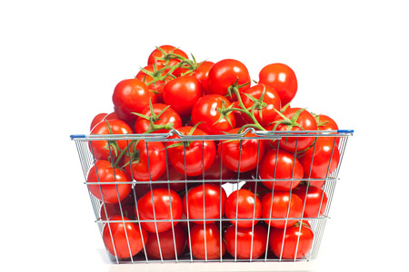 plating: There is a shopping basket full of red ripe tomatoe. Conceptual image of buying vegetables and healthy eating.