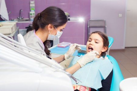 treating: Close-up of pretty little girl opening his mouth wide during treating her teeth by the dentist