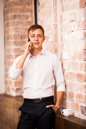 Handsome businessman in white shirt is speaking on the phone near the brick wall. There is a cup of coffee nearby Фото со стока - 75710324