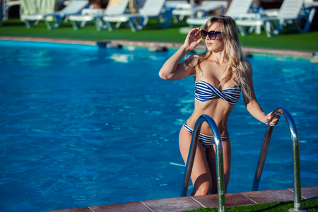 Mooie jonge vrouw in een mooie zwembroek staat op een trap in het zwembad. Ze lacht zo geweldig. Stockfoto