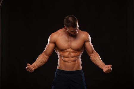 Modelo atlético fuerte de la aptitud del hombre Torso que muestra seis ABS del paquete. aislado en fondo negro con copyspace se está mirando a sí mismo Foto de archivo - 76090644