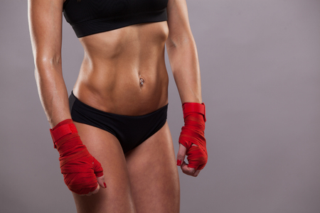 Close view of athletic girl posing in red bandages, isolated on the grey background boxing fighter kickbox Imagens - 76091053