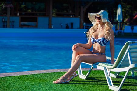 Beautiful young girl is sitting on the chaise-longue with pleasure near a swimming pool. She is wearing beautiful swimsuit, sunglasses and a hat