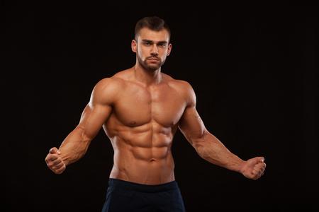 강한 체육 남자 휘트니스 모델 몸통 6 팩 복근을 보여주는. copyspace와 검은 배경에 고립 스톡 콘텐츠