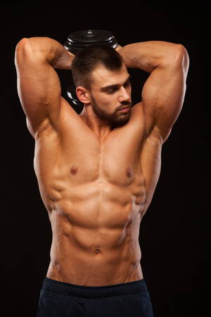 Strong man making exercises on triceps with a dumbbell. Close up shot training hands. Fitness Model showing his Torso with six pack abs. isolated on black background with copyspace Stock Photo