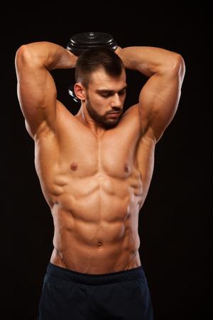 homme fort faire des exercices sur triceps avec un camarade de classe assis sur la table de fitness . modèle de perte de poids montrant ses barres avec le maquillage isolé fond noir avec des points de copyspace