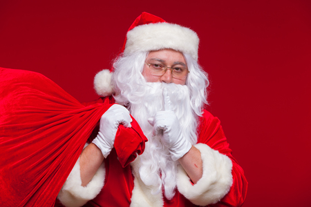 Portrait of Santa Claus with huge red sack keeping forefinger by his mouth and looking at camera Stock Photo