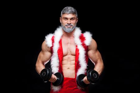 休日や行事、正月、クリスマス、スポーツ、ボディービル、健康的なライフ スタイル - 筋肉のハンサムなセクシーなサンタ クロース。ダンベルで黒