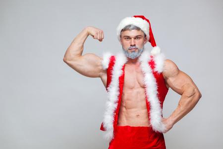 クリスマス。セクシーなサンタ クロース。サンタ クロースの帽子を身に着けている若い筋肉男は、彼の筋肉を示しています。