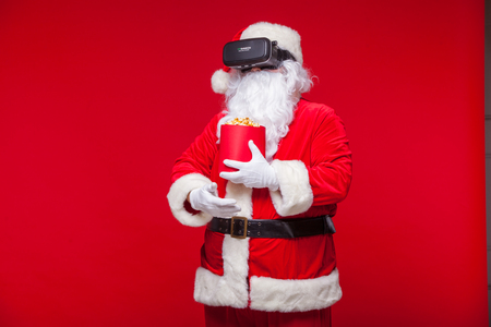 Santa Claus wearing virtual reality goggles and a red bucket with popcorn, on a red background. Christmas Stock Photo
