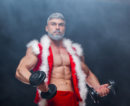 Holidays and celebrations, New year, Christmas, sports, bodybuilding, healthy lifestyle - Muscular handsome sexy Santa Claus. on a black background with dumbbells. in the smoke