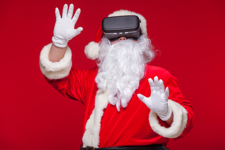 newyear: Santa Claus wearing virtual reality goggles, on a red background. Christmas Stock Photo