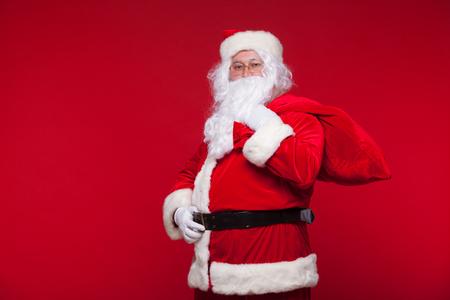 크리스마스. 어깨에 큰 가방을 가진 산타 클로스는 빨간색 배경에있다. 스톡 콘텐츠